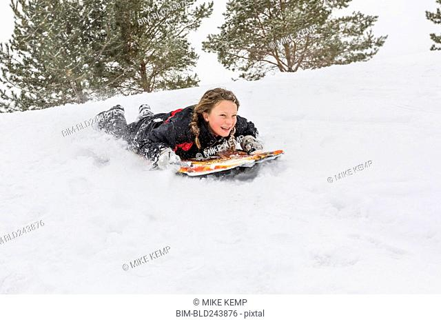 Smiling girl sliding on snowboard on hill in winter