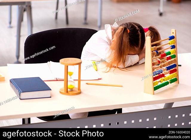 Small girl with the abacus in the classroom