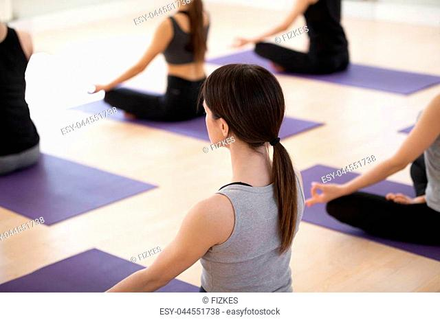 Group of young sporty people practicing yoga, doing Sukhasana exercise, Easy Seat pose, indoor close up view, students working out in sport club, studio