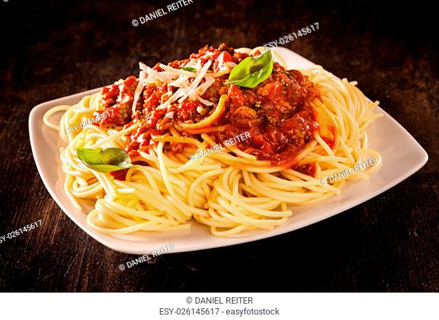 Italian spaghetti Bolognaise topped with a rich tomato and ground beef sauce garnished with fresh basil leaves and grated cheese