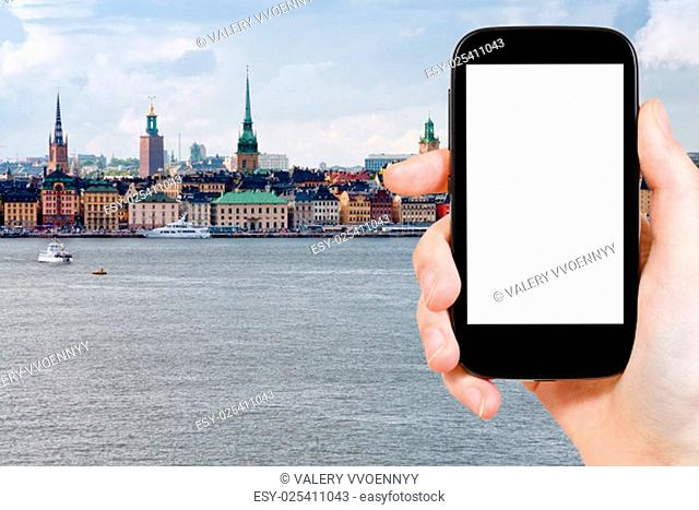 travel concept - tourist photograph skyline of Stockholm city , Sweden in autumn on smartphone with cut out screen with blank place for advertising logo