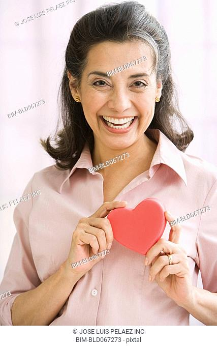 Hispanic woman holding heart-shaped object