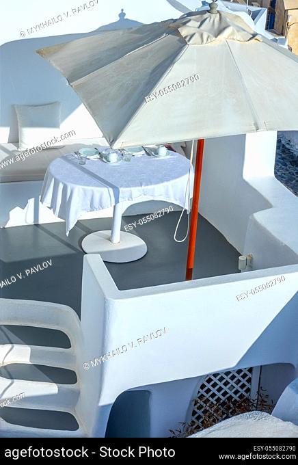 Greece. Sunny summer day on the caldera of Santorini island. Served table under a sun umbrella on the outdoor terrace
