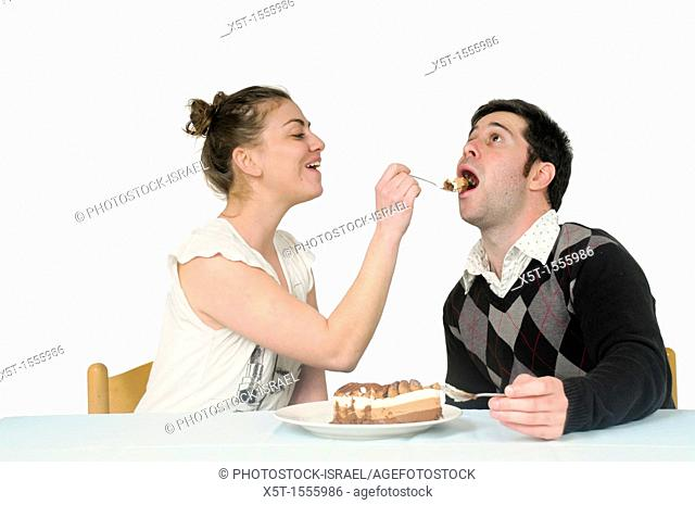 Woman feeds cream cake to a man
