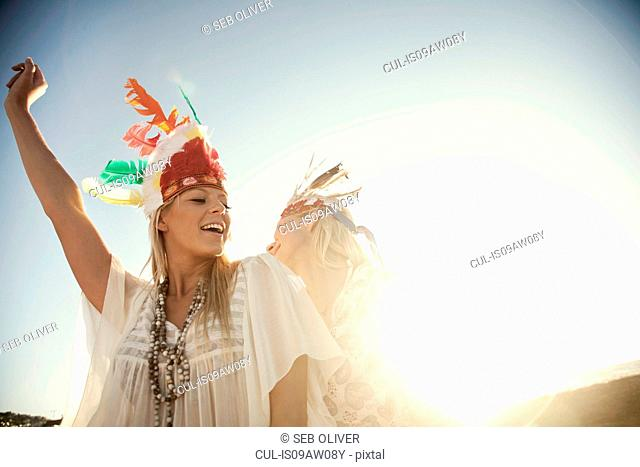 Young women wearing feather headdresses dancing in sunlight smiling