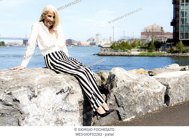 USA, Brooklyn, smiling mature woman sitting on a wall