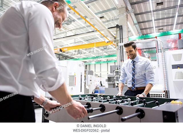 Two colleagues playing foosball in factory