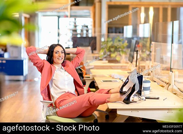 Relaxed female professional smiling while sitting with feet up at desk in office