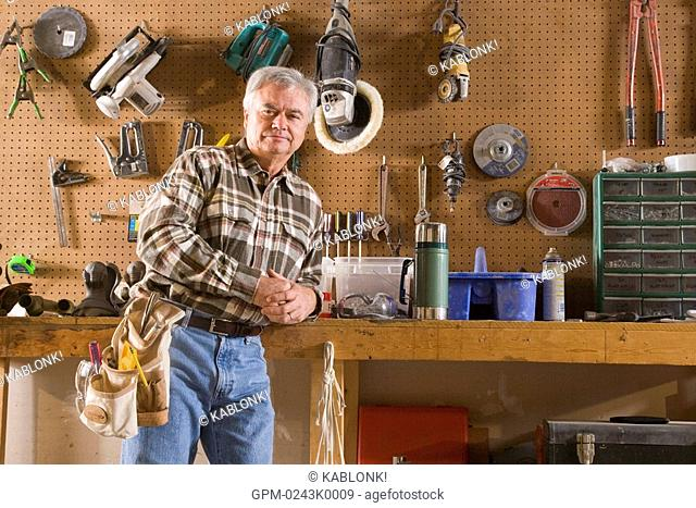 Portrait of senior man standing in garage with tools and tool belt, looking at camera