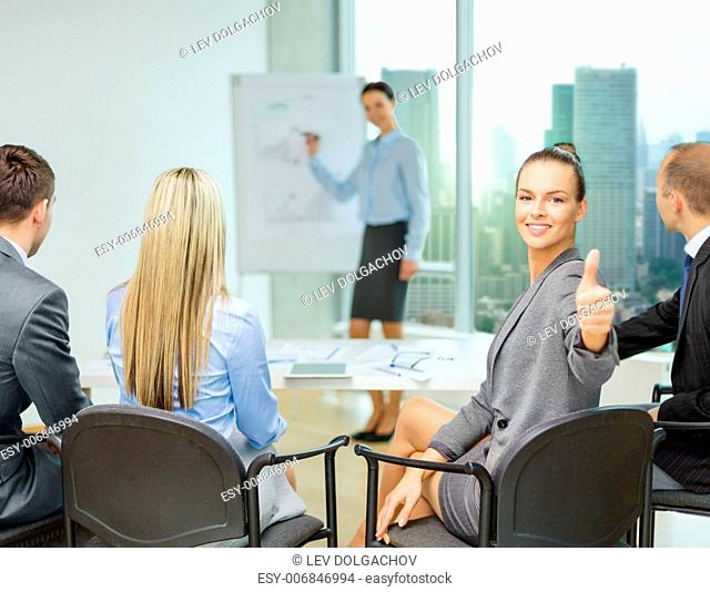 business, teamwork, people and success concept - happy businesswoman with team in office showing thumbs up