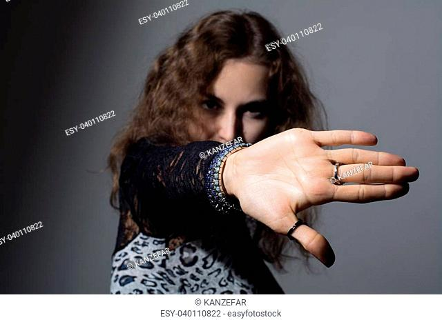 Out of focus woman with hand signaling to stop