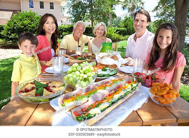 An attractive happy, smiling family of mother, father, grandparents, son and daughter eating healthy food at a picnic table outside