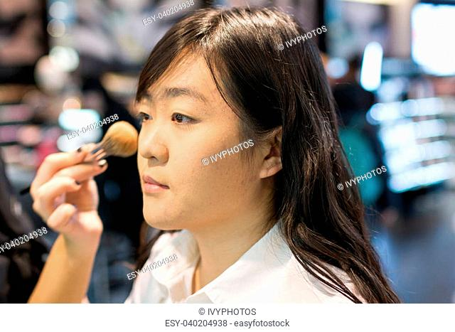Young Asian woman applying facial powder with a brush