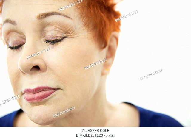 Face of older Caucasian woman with eyes closed