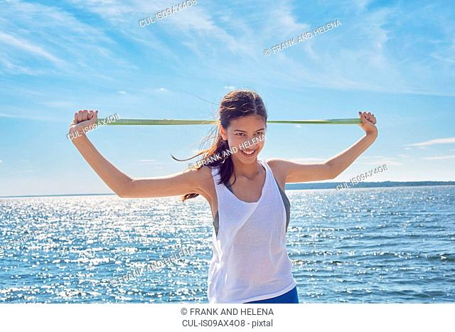 Woman in front of ocean holding resistance band looking at camera smiling