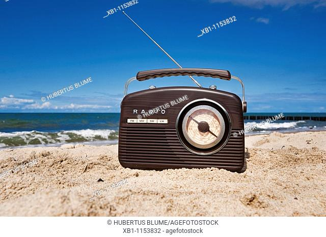 a radio stands on a sandy beach