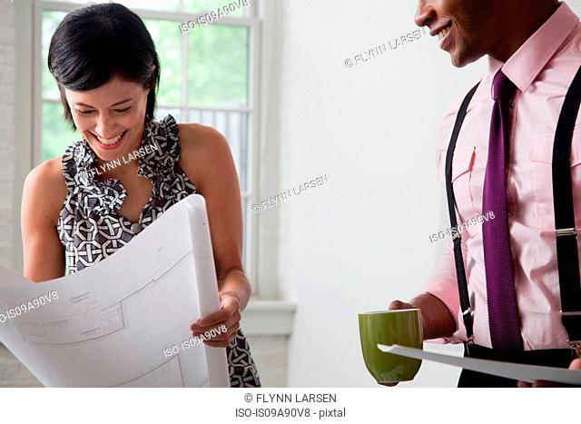 Office colleagues holding blueprints in office, smiling