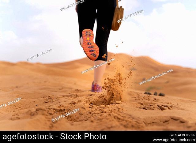 Feet of a woman running on sand dune in Sahara Desert, Merzouga, Morocco