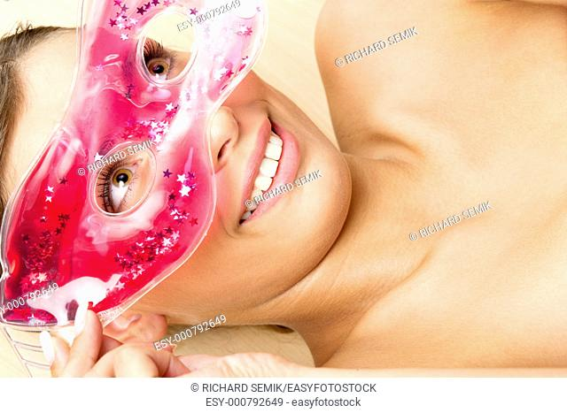 portrait of lying woman with cooling facial mask