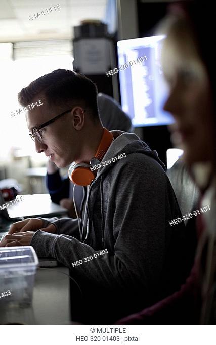 Focused male hacker working hackathon at laptops in dark office