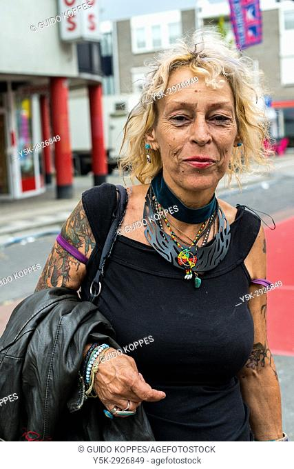 Tilburg, Netherlands. Mature adult caucasian woman strolling the annual fairgrounds during morning hours