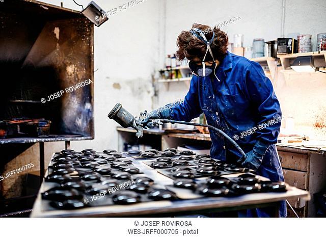 Female worker painting ceramics with spray gun