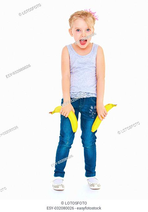 Cheerful little blonde girl in t-shirt and jeans holding two bananas - isolated on white background