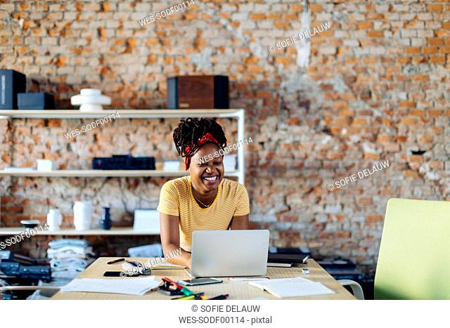 Happy young woman sitting at table with laptop