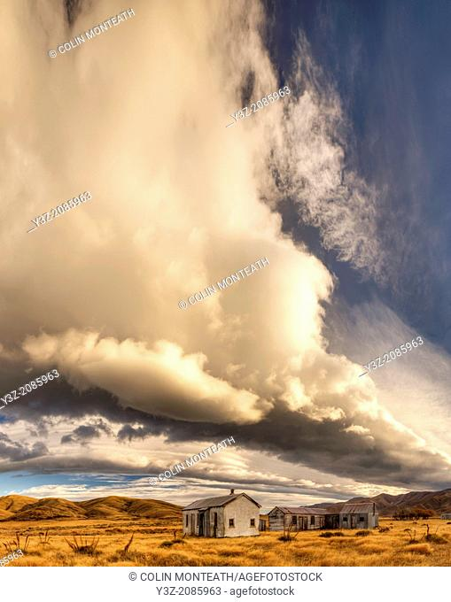 Dawn lights up cloudscape over historic (1939) farm buildings near St Bathans, Central Otago, New Zealand