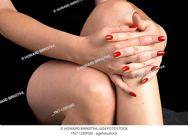close view of woman's hands folded across knees