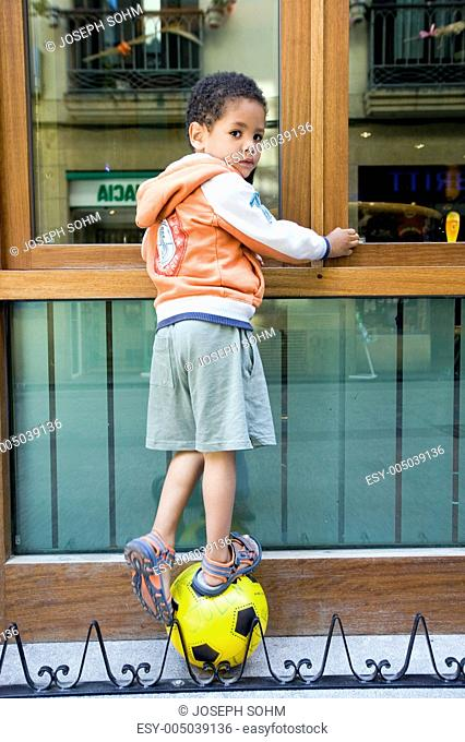 Little boy stands on soccer ball in old quarter Centro of Donostia-San Sebastian, Basque region of Spain, the Queen of Euskadis and Cantabrian Coast