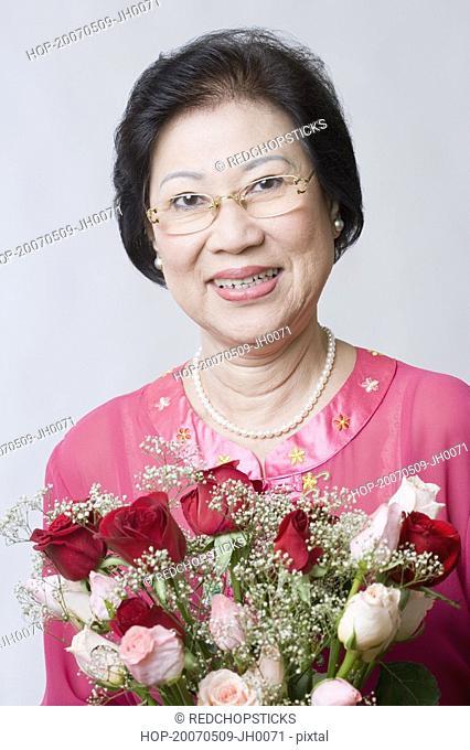 Portrait of a senior woman holding a bouquet of flowers