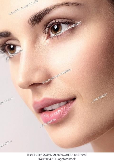 Closeup of a young beautiful woman face with brown eyes, clean natural look and smooth skin