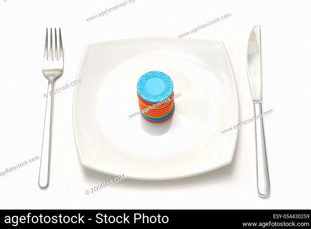 casino chips on white plate with fork and knife
