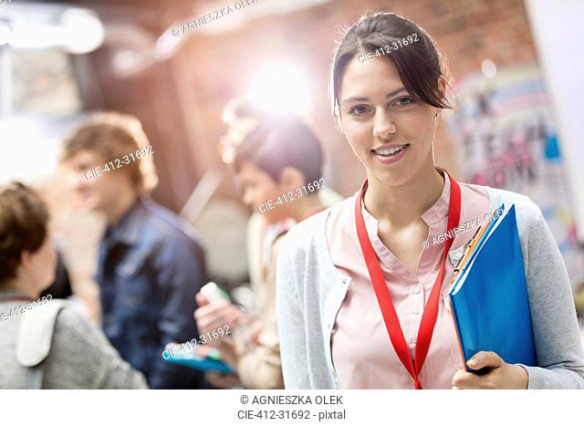 Portrait smiling woman holding folder at technology conference