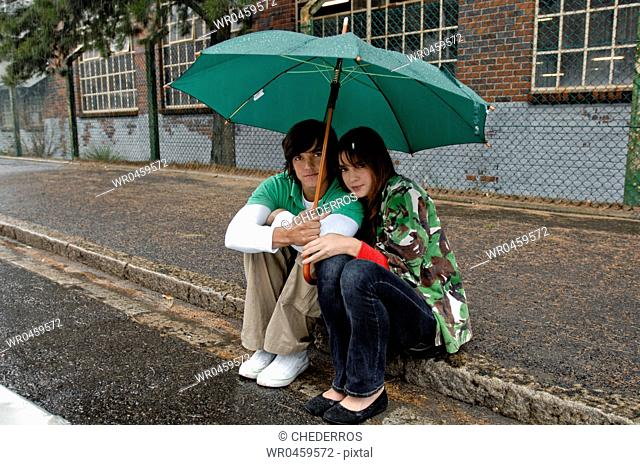 Young couple sitting together on the street under an umbrella