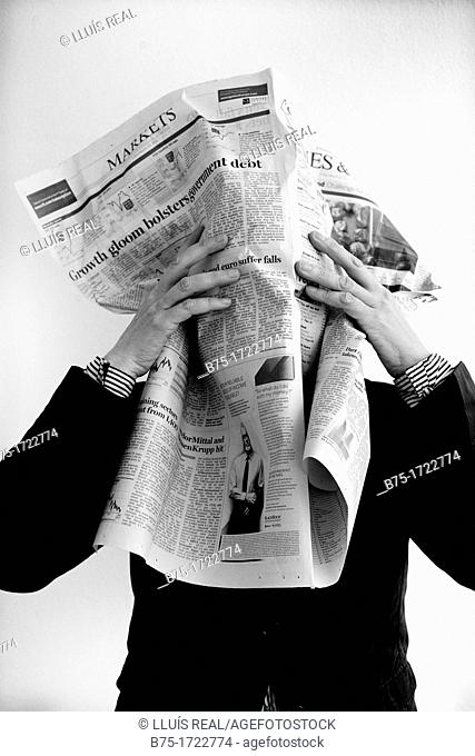 persona tapandose la cara con un periodico de economia, mercado de valores, person covering her face with a newspaper of economy, stock market