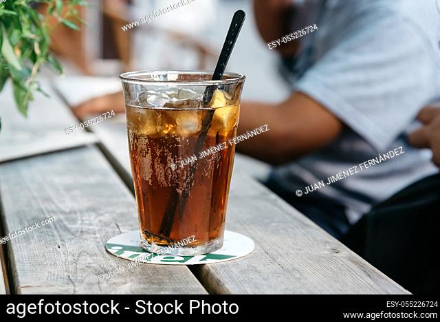 Refreshing glass of cola on wooden table in a bar