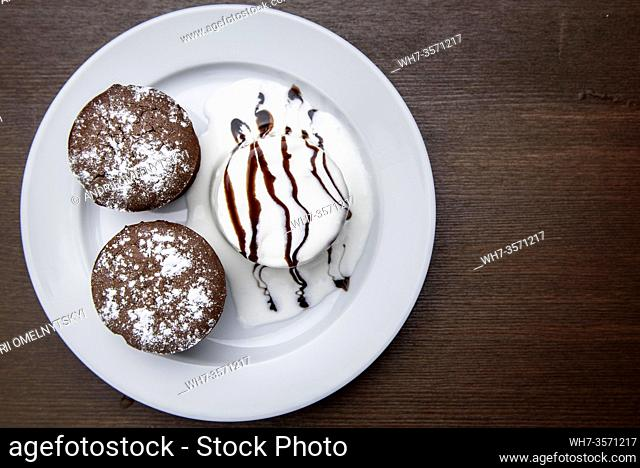 chocolate muffins with ice cream drizzled with chocolate topping