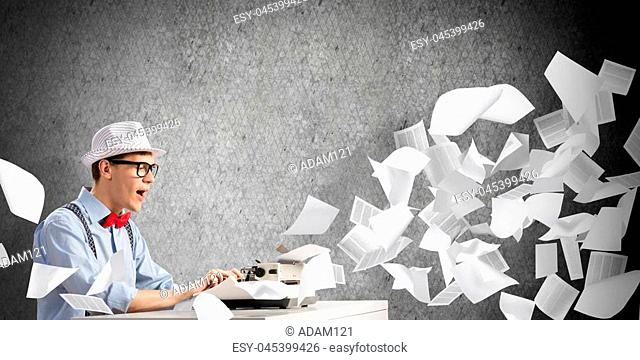 Young man writer in hat and eyeglasses using typing machine while sitting at the table among flying papers and against gray concrete wall on background