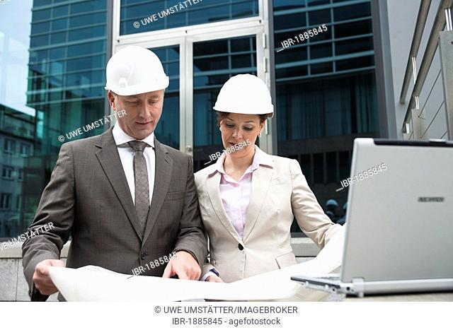 A male and a female architect checking a construction plan