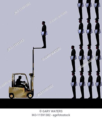 Forklift truck taking businessman from pile