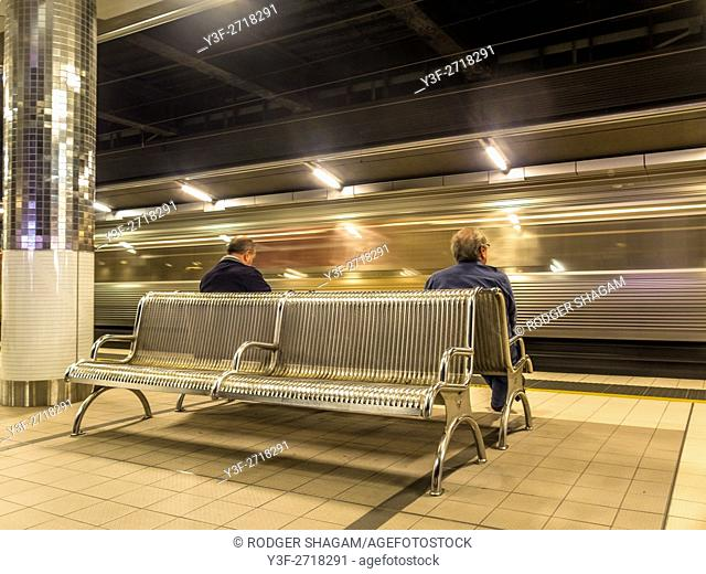 People sit and wait for the train to arrive as one flashes past in the opposite direction. An underground station. Cenral, Sydney, NSW, Australia