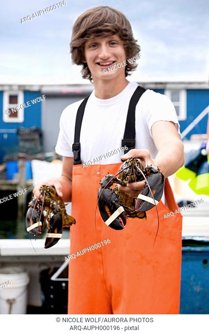 Teenage lobsterman apprentice shows off recent catch of lobsters