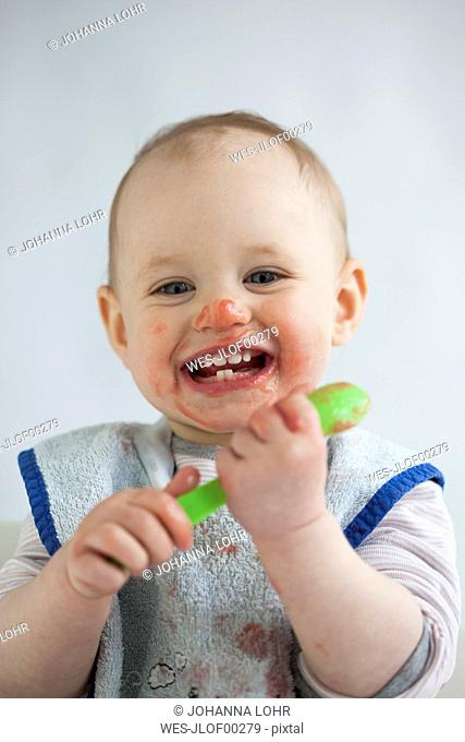 Portrait of laughing baby girl eating mush