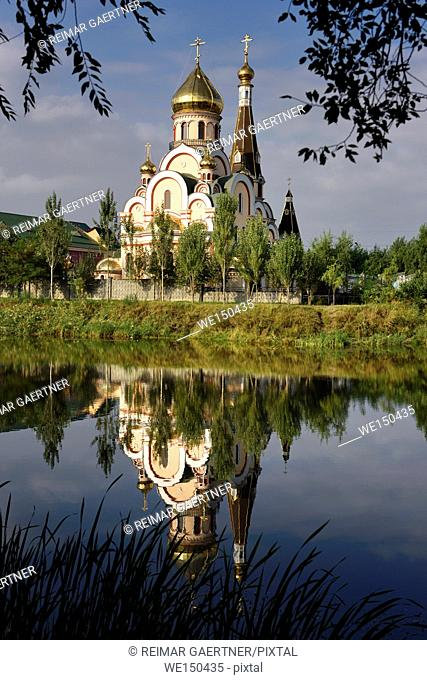 Orthodox Church of Exaltation of the Holy Cross in Almaty Kazakhstan reflected in pond water