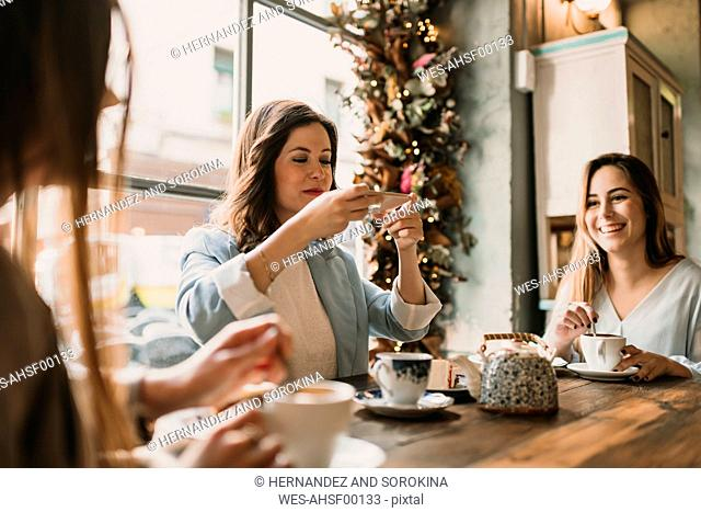 Young woman with friends taking a photo of cake and tea in a cafe