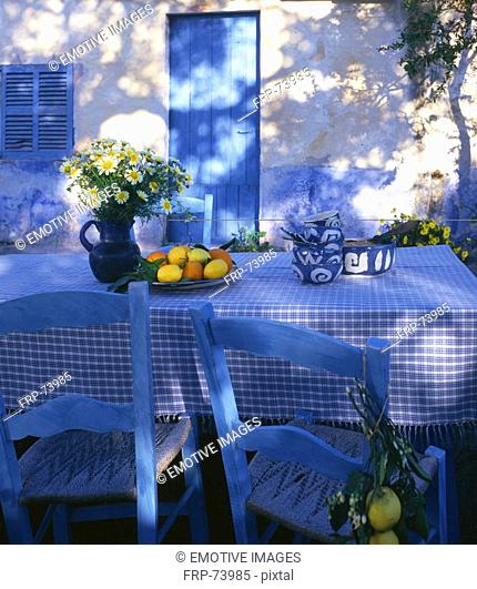 Blue and white table with lemons and oranges and a bouquet of marguerites