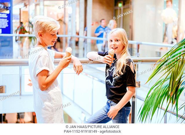 A boy and a girl eating icecream in a shopping mall, taken on 16/06/17 in Frankfurt (model released) | usage worldwide. - Frankfurt am Main/Hessen/Germany