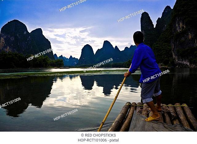 Side profile of a mature man rowing a wooden raft in a river, Li River, XingPing, Yangshuo, Guangxi Province, China